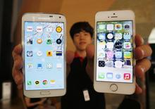 A sales assistant holding Samsung Electronics' Galaxy 5 smartphone (L) and Apple Inc's iPhone 5 smartphone (R) poses for photographs at a store in Seoul July 16, 2014. REUTERS/Kim Hong-Ji