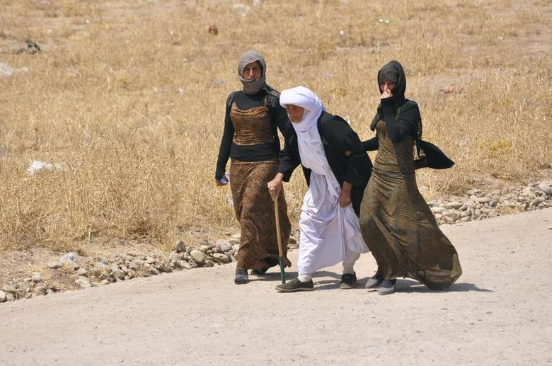 Displaced families from the minority Yazidi sect, fleeing the violence, walk on the outskirts of Sinjar, west of Mosul, August 5, 2014.  REUTERS/Stringer