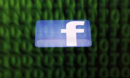 El logo de Facebook en la pantalla de un iPad que refleja código binario de un ordenador en Sarajevo, jun 18 2014. Facebook Inc dijo el jueves que adquirirá una compañía que ayuda a proteger computadoras y centros de datos a través de la encriptación de datos.   REUTERS/Dado Ruvic