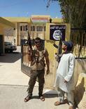 Militantes do Estado Islâmico de guarda após tomarem controle da sede do Partido Democrático do Curdistão na cidade de Bartella, no Iraque. 07/08/2014  REUTERS/Stringer
