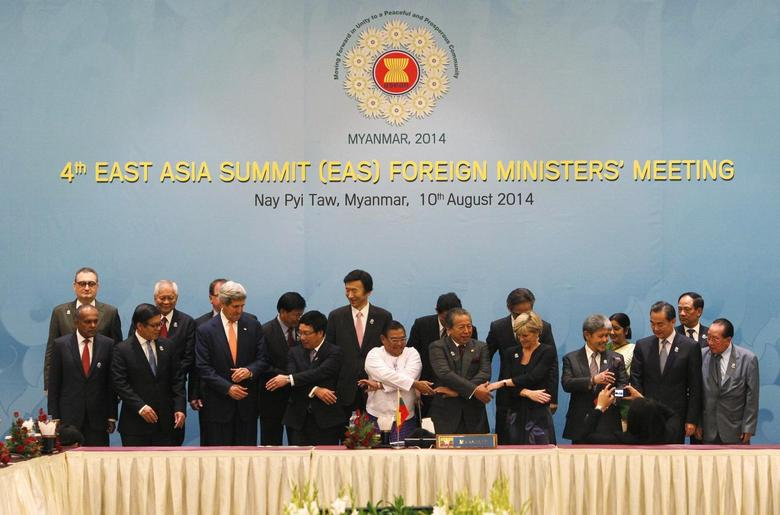 Dignitaries hold hands as they pose for a photo before the 4th East Asia Summit (EAS) Foreign Ministers Meeting at the Myanmar International Convention Centre (MICC) in Naypyitaw, August 10, 2014.    REUTERS/ Soe Zeya Tun