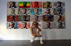 "Hungarian artist Kriszta ""Tereskova"" Nagy poses next to her portraits of Prime Minister Viktor Orban in Budapest August 5, 2014.  REUTERS/Laszlo Balogh"