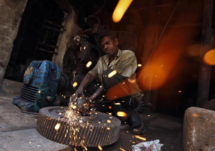 A man works inside a gear parts manufacturing unit at an industrial area in Kolkata July 11, 2014. REUTERS/Rupak De Chowdhuri