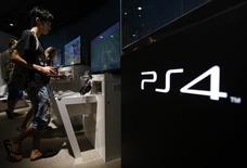 Un adolescente probando una consola playstation 4 en un salón de muestras de Sony en Tokio, jul 16 2014. La compañía japonesa Sony Corp dijo el martes que las ventas de su consola de videojuegos PlayStation 4 sobrepasaron las 10 millones de unidades desde el lanzamiento en noviembre del año pasado. REUTERS/Yuya Shino