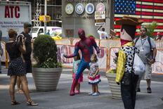 Pessoa vestida de Homem-Aranha posa para foto com crianças na Times Square, em Nova York. 11/08/2014 REUTERS/Lucas Jackson