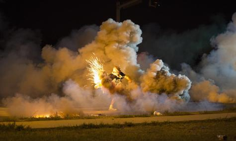A protester throws back a smoke bomb while clashing with police in Ferguson, Missouri August 13, 2014. REUTERS/Mario Anzuoni