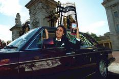 Cantor Cliff Richard mostra medalha ao deixar o Palácio de Buckingham, em Londres, depois de receber a condecoração da rainha Elizabeth. 25/10/1995 REUTERS/Dylan Martinez/Files
