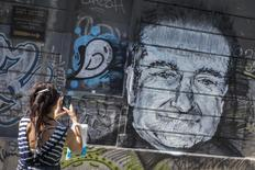 A woman takes a picture of a mural depicting late actor Robin Williams in Belgrade, August 13, 2014.    REUTERS/Marko Djurica