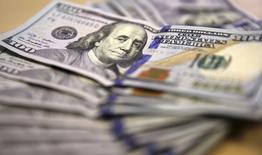 Американские доллары в Йоханнесбурге 13 августа 2014 года. Доллар снизился против корзины валют в понедельник на фоне снижения доходности облигаций американского казначейства почти до минимума 16 месяцев. REUTERS/Siphiwe Sibeko