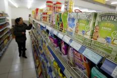 Chinese customers select food on a shelf where Heinz products are displayed in a market in Shanghai March 15, 2006. REUTERS/Stringer