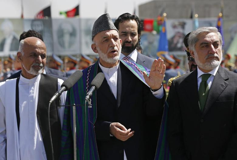 Afghan President Hamid Karzai (C) speaks during celebrations to commemorate Afghanistan's 95th anniversary of independence as he is flanked by presidential candidates Abdullah Abdullah (R) and Ashraf Ghani in Kabul August 19, 2014. REUTERS/Omar Sobhani