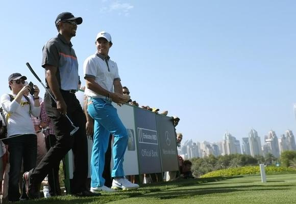 Tiger Woods of the U.S. and Rory McIlroy of Northern Ireland walk to the 8th tee during the first round of the 2014 Omega Dubai Desert Classic in Dubai January 30, 2014.  REUTERS/Caren Firouz