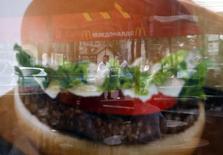 Люди отражаются в двери закрытого ресторана McDonald's в Москве 21 августа 2014 года. Российский регулятор сообщил в четверг, что начал проверки ресторанов американской сети McDonald's в Свердловской области, на следующий день после временного закрытия четырех ресторанов в Москве. REUTERS/Maxim Zmeyev