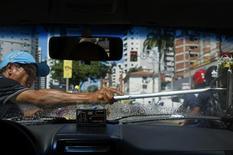 Una persona limpia el parabrisas de un vehículo a cambio de monedas en una calle de Fortaleza, jun 25 2014. El estatal Instituto Brasileño de Geografía y Estadística de Brasil divulgará los datos de desempleo correspondientes a los meses de mayo hasta agosto el 25 de septiembre, debido a que una huelga interrumpió el principal sondeo del mercado laboral del país, dijo el jueves el IBGE.  REUTERS/Marcelo del Pozo