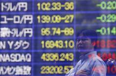 Мужчина изучает табло с котировками в Токио 10 июня 2014 года. Азиатские фондовые рынки завершили торги пятницы и неделю разнонаправленно под влиянием местных факторов и накануне выступления председателя ФРС Джанет Йеллен. REUTERS/Issei Kato