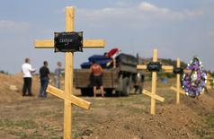 """Рабочие разгружают грузовик с гробами на кладбище шахты №6 """"Капитальная"""" в Донецке 21 августа 2014 года. Пророссийские сепаратисты несут такие тяжелые потери в боях с наступающими правительственными войсками, что у них больше нет времени устраивать похороны всем своим погибшим товарищам. REUTERS/Maxim Shemetov"""