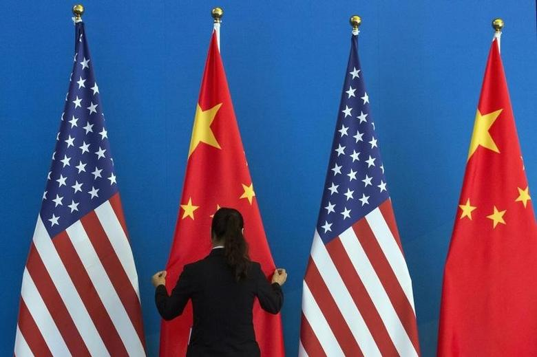 A Chinese woman adjusts a Chinese national flag next to U.S. national flags before a Strategic Dialogue expanded meeting, part of the U.S.-China Strategic and Economic Dialogue (S&ED) held at the Diaoyutai State Guesthouse in Beijing, July 10, 2014. REUTERS/Ng Han Guan/Pool