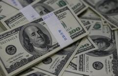 Imagen de archivo de unos billetes de 100 dólares amontonados para una ilustración fotográfica en un banco de Seúl, ago 2 2013. El déficit del Gobierno de Estados Unidos en el año fiscal 2014 podría llegar a 506.000 millones de dólares, algo más que los 492.000 millones de dólares que se anticipaban en abril, debido a una menor recaudación de impuestos de las empresas, dijo el miércoles la Oficina de Presupuesto del Congreso. REUTERS/Kim Hong-Ji