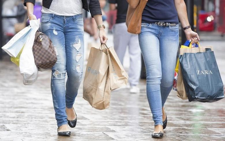 Shoppers carry bags as they walk along Oxford Street in central London July 25, 2014.   REUTERS/Neil Hall