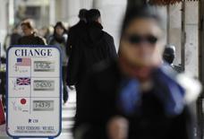 Люди проходят мимо пункта обмена валюты в Париже 27 февраля 2008 года. Евро готовится завершить второй месяц подряд в минусе из-за ухудшения ситуации на Украине. REUTERS/Gonzalo Fuentes