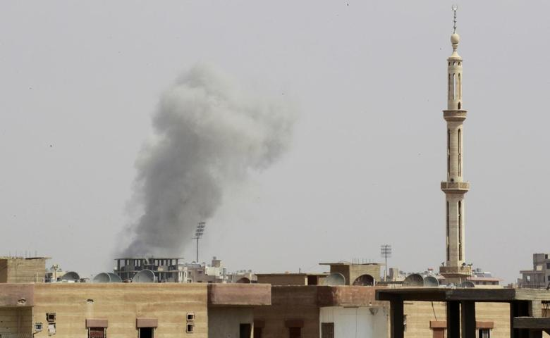 Smoke rises after what activists said was an air raid by Syrian government forces at the eastern Syrian city of Raqqa August 18, 2014. REUTERS/Stringer
