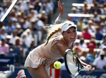 Caroline Wozniacki of Denmark misses as she reaches for a return to Peng Shuai of China during their semi-final match at the 2014 U.S. Open tennis tournament in New York, September 5, 2014. REUTERS/Adam Hunger