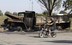 Мотоциклист проезжает мимо сгоревшего грузовика под Мариуполем 7 сентября 2014 года. Организация по безопасности и сотрудничеству в Европе признала, что подписанный на прошлой неделе мирный протокол, обязывающий пророссийских сепаратистов и украинские силы прекратить огонь, в целом соблюдается, несмотря на обстрелы, которые стали происходить реже. REUTERS/Vasily Fedosenko