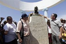 """John Hemingway (a la izquierda) y Patrick Hemingway (a la derecha), nietos del escritor estadounidense Ernest Hemingway, brindan tributo a su abuelo en su estatua en la villa Cojimar, en Cuba, 8 de septiembre del 2014.  Los nietos de Ernest Hemingway navegaron en un yate el lunes hasta llegar al pueblo de pescadores que inspiró a su abuelo a escribir """"El Viejo y el Mar"""", en una campaña para impulsar la pesca deportiva de las agujas como la que arrastró al mar al ficticio personaje Santiago de su afamada novela. REUTERS/Enrique De La Osa"""