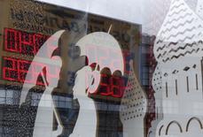 Отражение табло с курсами обмена валют в витрине магазина в Москве 29 августа 2014 года. Рубль прервал утреннюю спячку в среду и ушел в минус в русле тенденций мировых рынков, где инвесторы перекладываются в американский доллар из рискованных активов, а нефть обновляет многомесячные минимумы. REUTERS/Sergei Karpukhin
