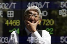 Отражение прохожего у брокерской конторы в Токио 11 апреля 2014 года. Азиатские фондовые рынки завершили пятницу и неделю разнонаправленно, в основном, опираясь на местные факторы. REUTERS/Issei Kato