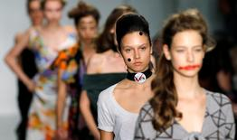 """Wearing a """"Yes"""" badge, in reference to Scotland's independence referendum, a model presents a creation from the Vivienne Westwood Red Label Spring/Summer 2015 collection during London Fashion Week September 14, 2014. REUTERS/Suzanne Plunkett"""