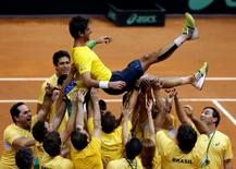 Brazil's team members throws up Thomaz Bellucci after he defeated Roberto Bautista of Spain at their Davis Cup play-off tennis match in Sao Paulo September 14, 2014. REUTERS/Paulo Whitaker