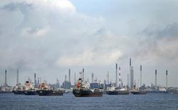 Суда у НПЗ в Сингапуре 6 июля 2014 года. Цены на нефть Brent упали до минимума более двух лет ниже $97 за баррель из-за слабых макроэкономических показателей Китая - одного из крупнейших в мире потребителей энергоносителей. REUTERS/Tim Wimborne