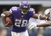 Minnesota Vikings Adrian Peterson runs with ball against the Dallas Cowboys in the first quarter at AT&T Stadium in Arlington, Texas in this file photo taken November 3, 2013. REUTERS/Matthew Emmons-USA TODAY Sports/Files