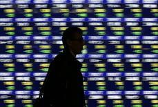 Прохожий у брокерской конторы в Токио 14 января 2014 года. Азиатские фондовые рынки завершили торги четверга разнонаправленно под влиянием локальных факторов. REUTERS/Issei Kato