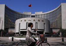 A woman rides past the headquarters of the People's Bank of China, the Chinese central bank, in Beijing, April 3, 2014.   REUTERS/Petar Kujundzic/Files