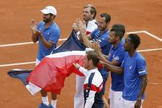 (From L, visible faces) French team captain Arnaud Clement, Julien Benneteau, Michael Llodra, Jo-Wilfried Tsonga, Gael Monfils and Richard Gasquet (front) react after their victory over Czech Republic in the semi-final of the Davis Cup at the Roland Garros stadium in Paris September 14, 2014. REUTERS/Charles Platiau