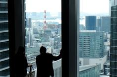 A man and a woman watch outside at the lobby of an office building in Tokyo September 17, 2014. REUTERS/Toru Hanai