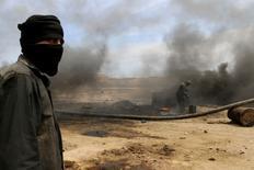 Работники мини-НПЗ в курдской части Сирии 11 мая 2014 года. Исламское государство, взявшее под контроль многие районы Ирака и Сирии, зарабатывает продажей нефти с месторождений на подконтрольных территориях. REUTERS/Rodi Said
