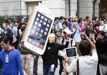 """Un hombre disfrazado de Steve Jobs sostiene una recreación en cartón de un iPhone 6 a las afueras de una tienda de Apple en Tokio, sep 19 2014. El nuevo iPhone atrajo a multitudes de fanáticos, emprendedores y desesperados por los dispositivos electrónicos a las tiendas de Apple Inc en Nueva York, San Francisco y otras ciudades de todo el mundo, en otra señal de la fuerte demanda que despierta la versión más grande del emblemático """"smartphone"""". REUTERS/Yuya Shino"""