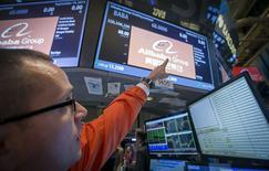 Трейдер указывает на тикер Alibaba во время IPO компании на Нью-Йоркской фондовой бирже 19 сентября 2014 года. IPO китайского гиганта интернет-торговли Alibaba сейчас можно назвать самым крупным за всю историю рынка, так как объем размещения составил $25 миллиардов после доразмещения акций в итоге реализации его организаторами опционов. REUTERS/Brendan McDermid