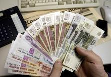 Человек держит в руках рублевые купюры в Санкт-Петербурге 18 декабря 2008 года. Рубль дорожает утром среды на фоне продаж экспортной выручки перед уплатой НДПИ и снижения локального спроса на валюту.  REUTERS/Alexander Demianchuk