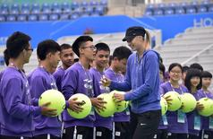 Maria Sharapova (front R) of Russia signs an autograph on a giant tennis ball as she talks to ball boys and girls during a promotional event ahead of the Wuhan Open Tennis Tournament in Wuhan, Hubei province September 18, 2014. REUTERS/China Daily