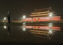 Un policía y el frontis del Tiananmen reflejados en agua en la plaza Tiananmenn en Beijin. Imagen de archivo, 22 septiembre, 2014.  La economía de China probablemente crecerá en el 2015 más rápido que lo previsto anteriormente, dijo el miércoles el Fondo Monetario Internacional, restando importancia a los riesgos de un enfriamiento en el mercado inmobiliario de la segunda economía más grande del mundo. REUTERS/Stringer