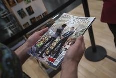 A customer holds a copy of Astonishing X-Men #51 while standing in line to purchase the comic book at a comic book retail shop in Manhattan, New York June 20, 2012.  REUTERS/Adrees Latif