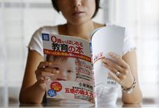 "Sayaka Osakabe, founder of ""Matahara net,"" a support group calling for legislation outlining more support for working women, reads an educational magazine for expectant mothers in their first trimester, in her house in Kawasaki, south of Tokyo September 11, 2014.   REUTERS/Yuya Shino"