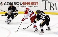 Carolina Hurricanes center Jordan Staal (11) handles the puck against pressure from Pittsburgh Penguins left wing Tanner Glass (15) during the second period at the CONSOL Energy Center. Apr 1, 2014; Pittsburgh, PA, USA; Charles LeClaire-USA TODAY Sports