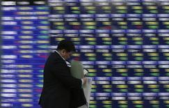 Un hombre pasa frente a una pizarra eléctronica con índices económicos en Tokio. Imagen de archivo, 04 diciembre, 2014.  Las bolsas de Asia se desplomaron el lunes a mínimos de cuatro meses debido a que la agitación política en Hong Kong inquietó a los inversores, mientras que el dólar se afirmaba gracias a unos datos que mostraron que la mayor economía estadounidense está bien encaminada. REUTERS/Toru Hanai