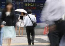Una mujer sujeta una sombrilla frente una pantalla que muestra índices económicos en Tokio. Imagen de archivo, 25 septiembre, 2014. Las bolsas de Asia se encontraban en un estado de ánimo indeciso el martes mientras los inversores se preguntaban cuál será la respuesta de China a los disturbios civiles en Hong Kong, mientras que el dólar retrocedía levemente aunque aún se encamina a su mayor ganancia mensual en más de un año. REUTERS/Toru Hanai