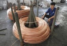 Un trabajador revisa la producción de rollos de cobre en una fábrica en Vietnam, afuera de Hanoi. Imagen de archivo, 02 noviembre, 2013. El cobre caía el martes, en camino a su mayor baja mensual desde marzo, ante un dólar más fuerte y nuevas señales de un alza en la oferta global y escasa demanda desde China, donde un sondeo industrial fue revisado con una leve baja. REUTERS/Kham